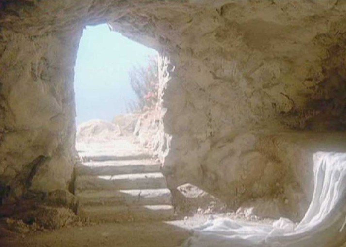 Light streams into an empty tomb, falling on discarded robes. The dark interior is in contrast to the bright sky which can be seen through the doorway